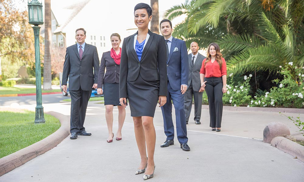 A group of MBA students in suits outside