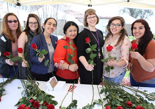 Library staff hand out books and roses to students