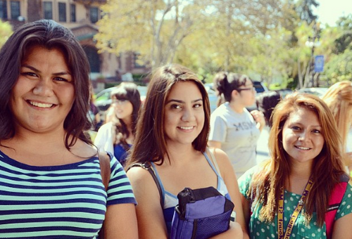 A group of three students pose in front of the Doheny Mansion during orientation
