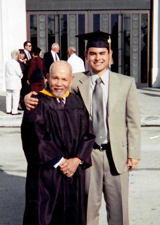 Che Ruddell-Tabisola '04, right, at the graduation of his father, Angelino Gonzalez Tabisola '99. Both are Weekend/Evening College alums.
