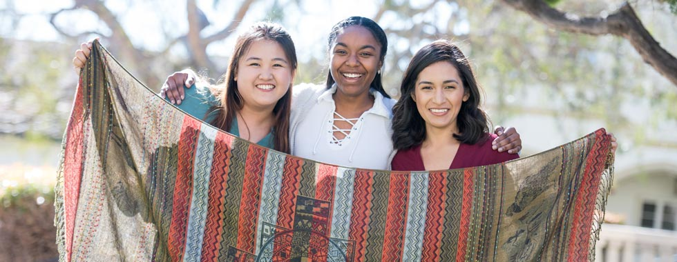Pauline Cheng '19, Janae Jones '19 and Erica Cisneros '18 hold up a woven blanket made in Peru.