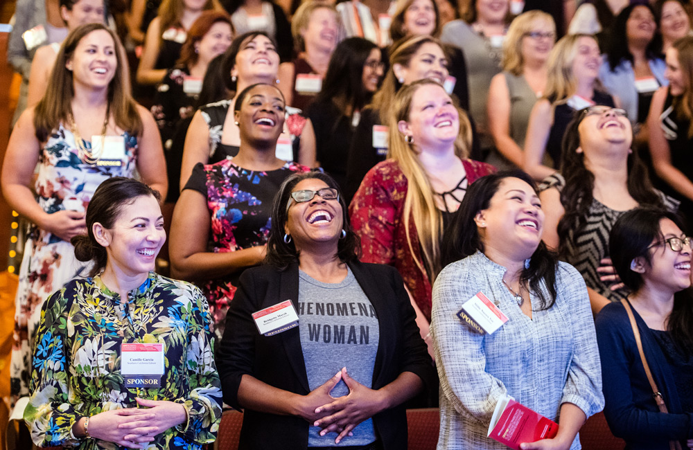 "Women's Leadership Conference attendees practice their ""Spirit of Joy"" with opening keynote speaker Dr. Susanne Bennett, DC. Did you know the average adult only laughs four times a day? As Dr. Bennett reminded everyone, laughter has the power to sustain and propel you forward."