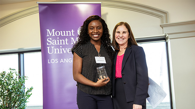 student standing with president of university with award