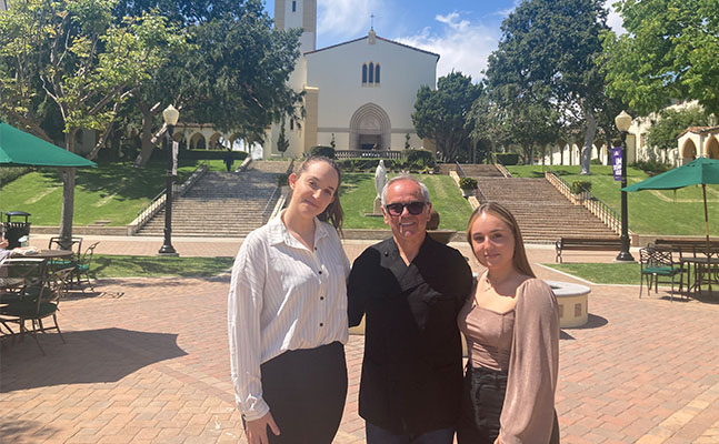 students sitting on school entrance sign