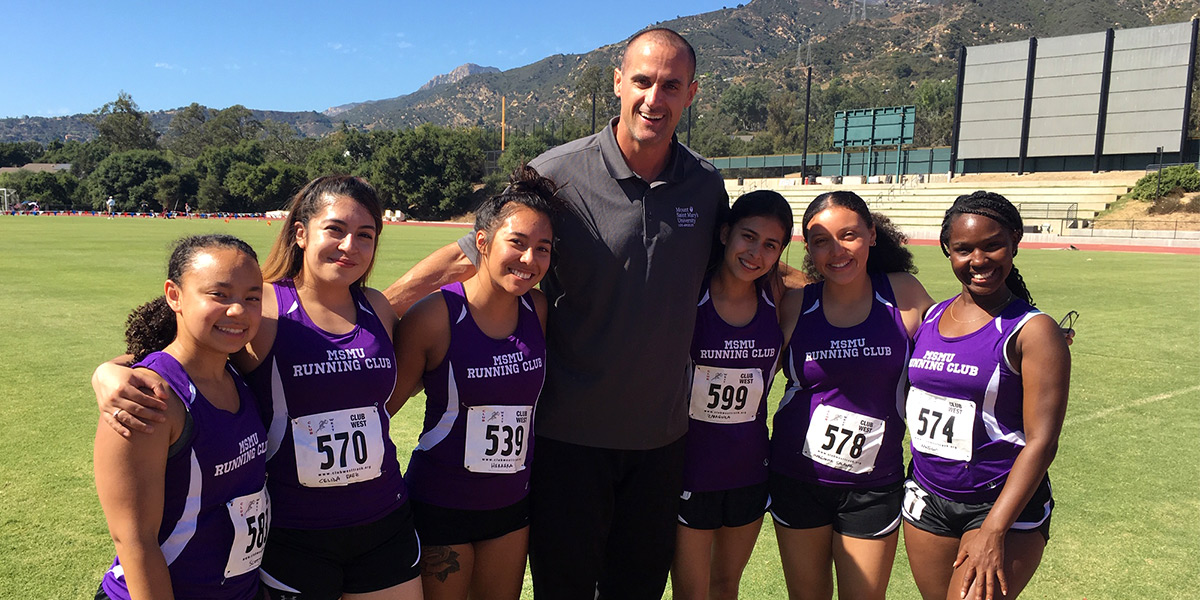 Coach Radenko Miskovic is surrounded by running club members at a recent open meet.