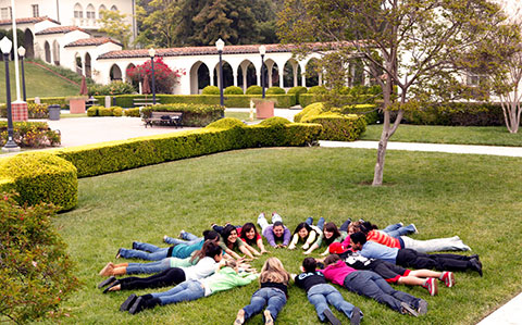 Multiple girls lay in a circle on the Admin Lawn