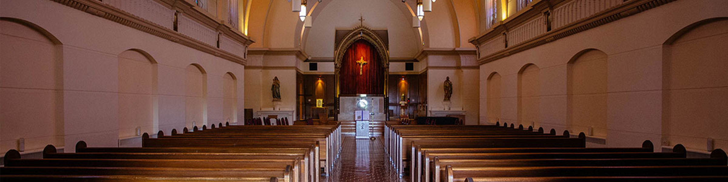 aisle in church with red curtains at altar