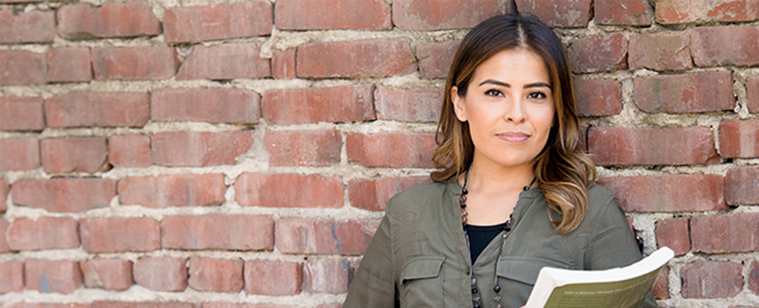 woman in green shirt smiling against brick wall holding book
